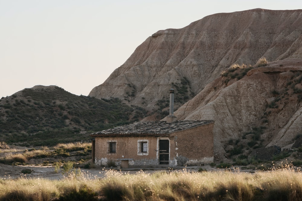 brown shed under mountain