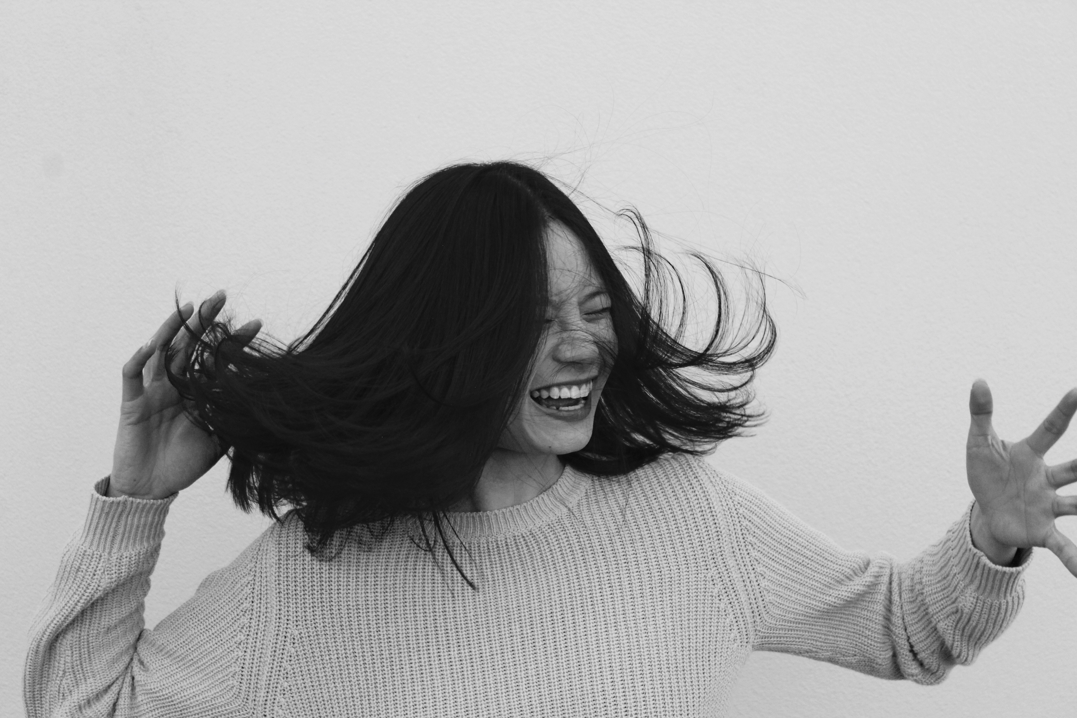 grayscale photo of woman flicking hair
