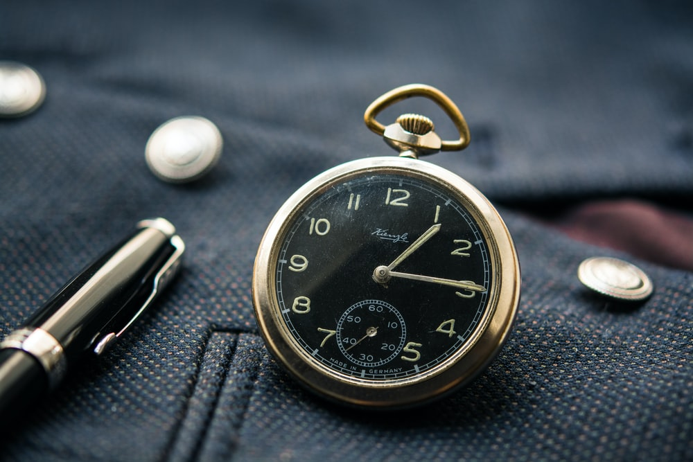 round silver-colored and black pocket watch displaying 1:15