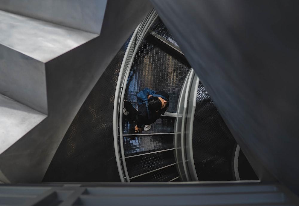 man walking on spiral stairs