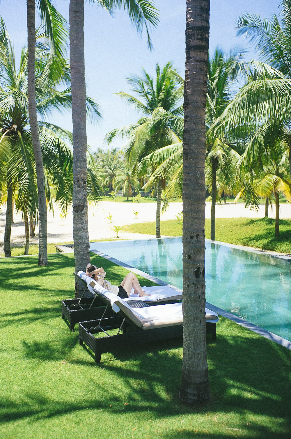person lying on lounge chair near pool