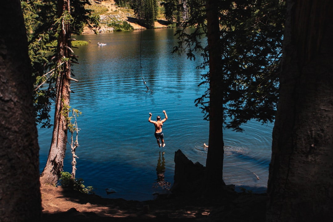 Image of a young Utahn taking the plunge into Bloods Lake, Park City UT. The Summers here can get pretty steamy so a hike and swim in one of Utah's many alpine lakes are on the brain.
