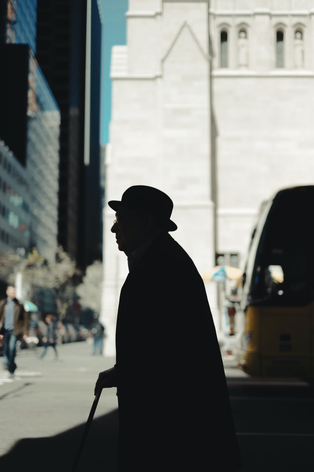 silhouette of man holding walking cane on road during daytime
