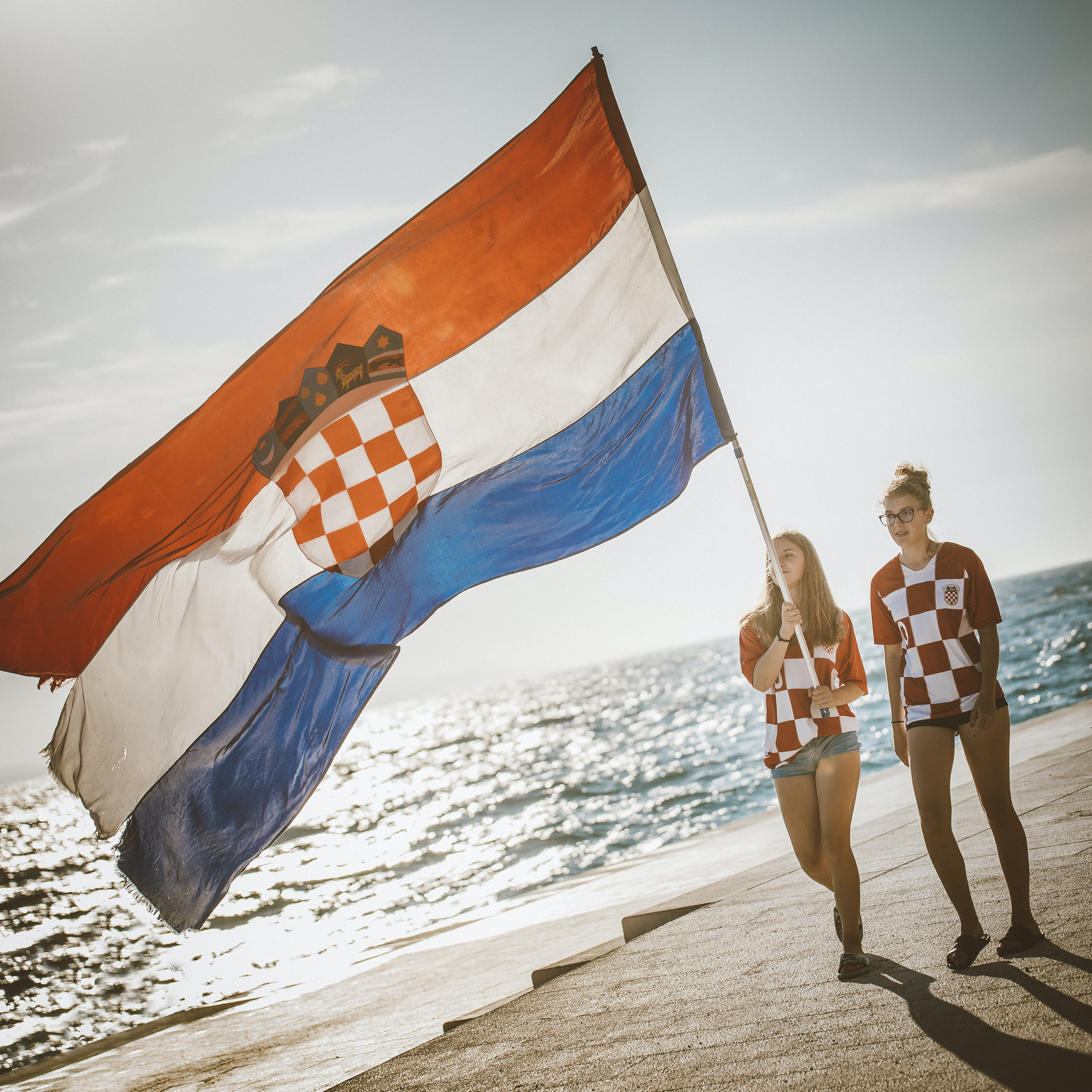 person holding country flag in beach