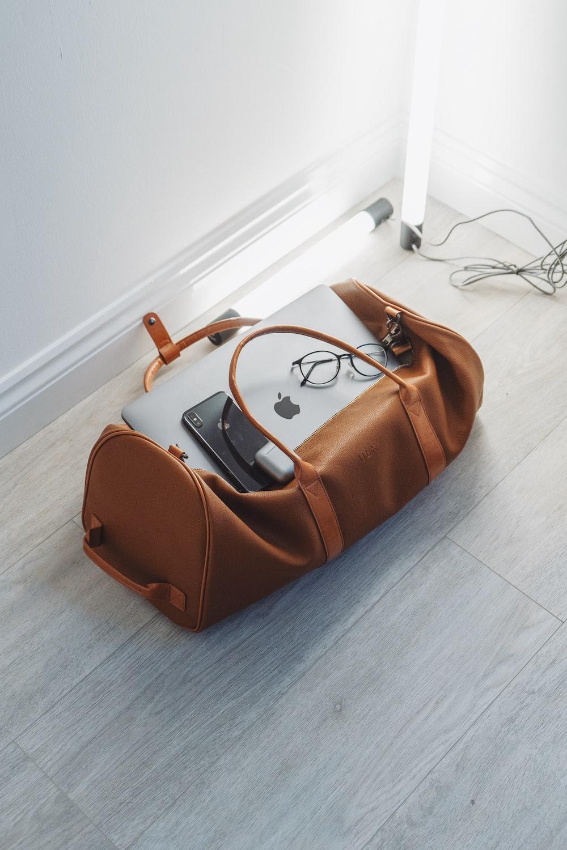 silver MacBook in duffel bag