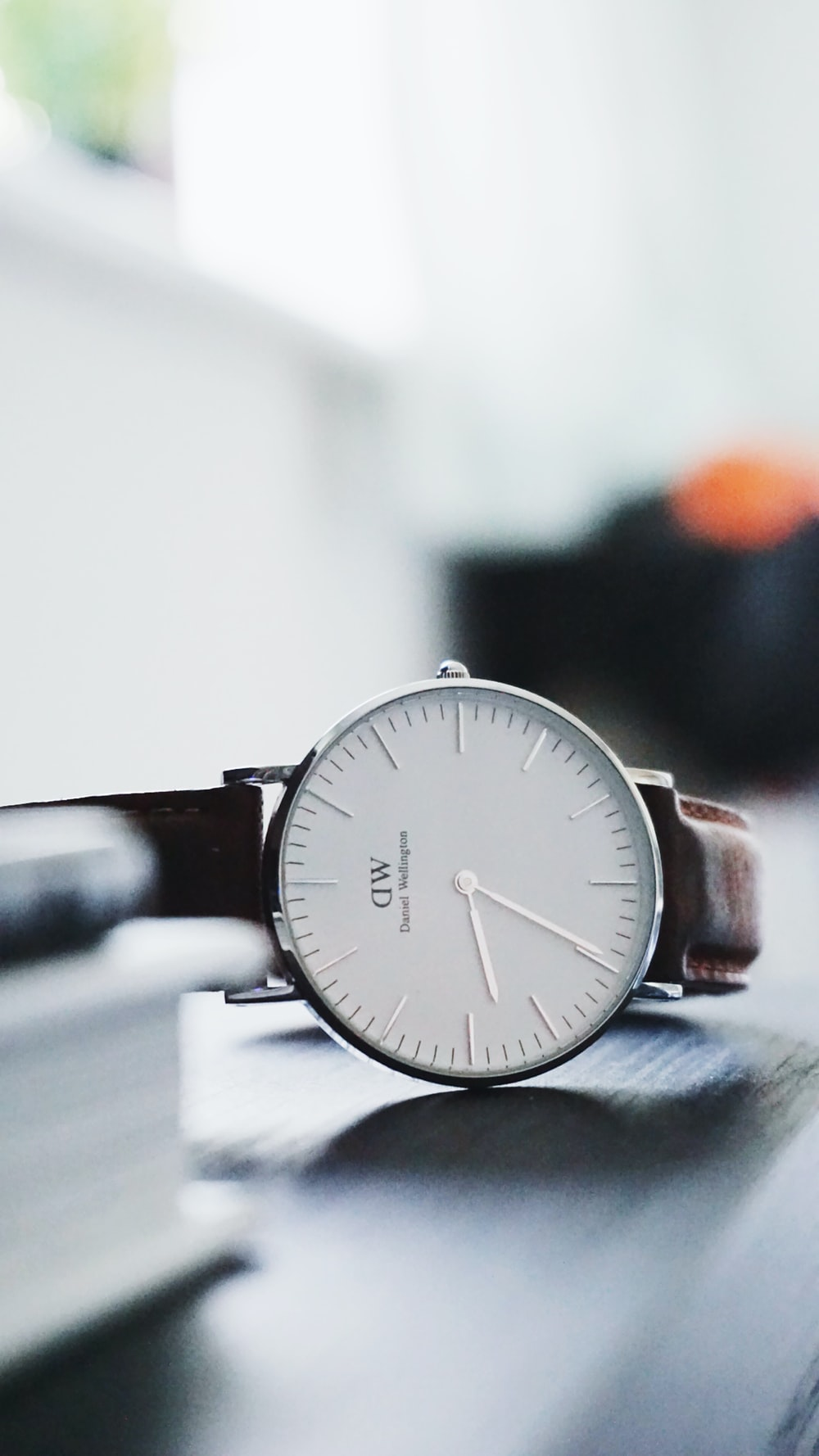 round silver-colored DW analog watch at 6:38