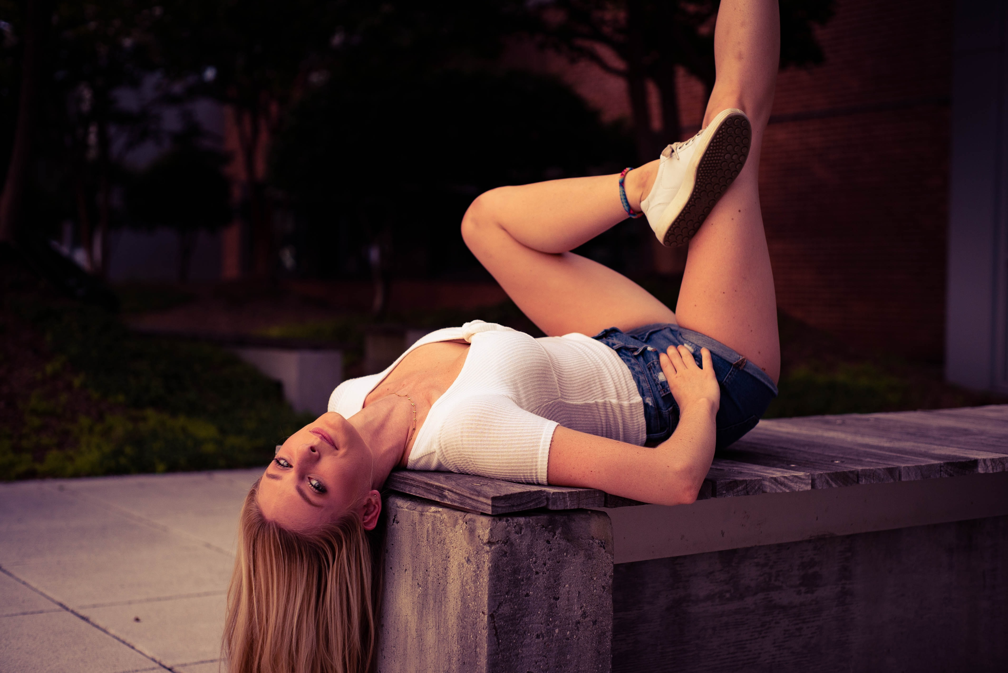 woman laying on bench outdoor