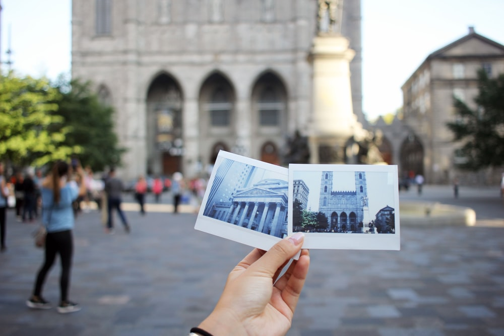 person holding two photo of buildings