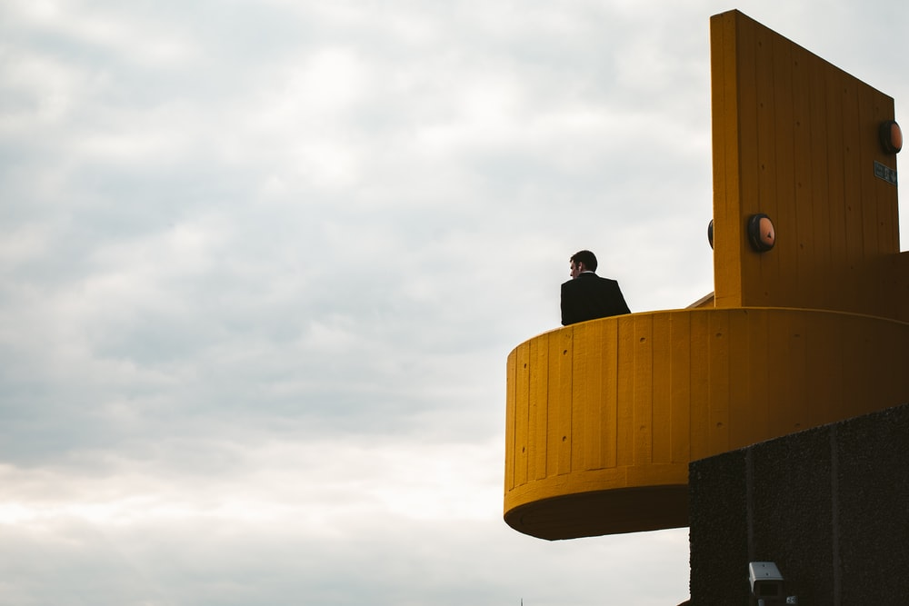 man standing on building under cloudy sky