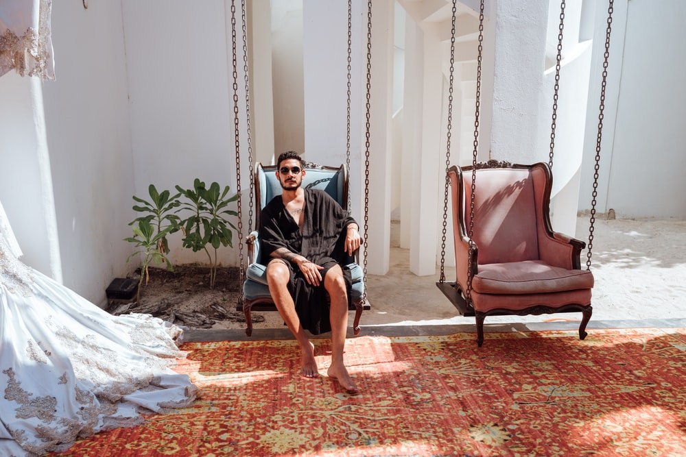 man sitting on blue armchair