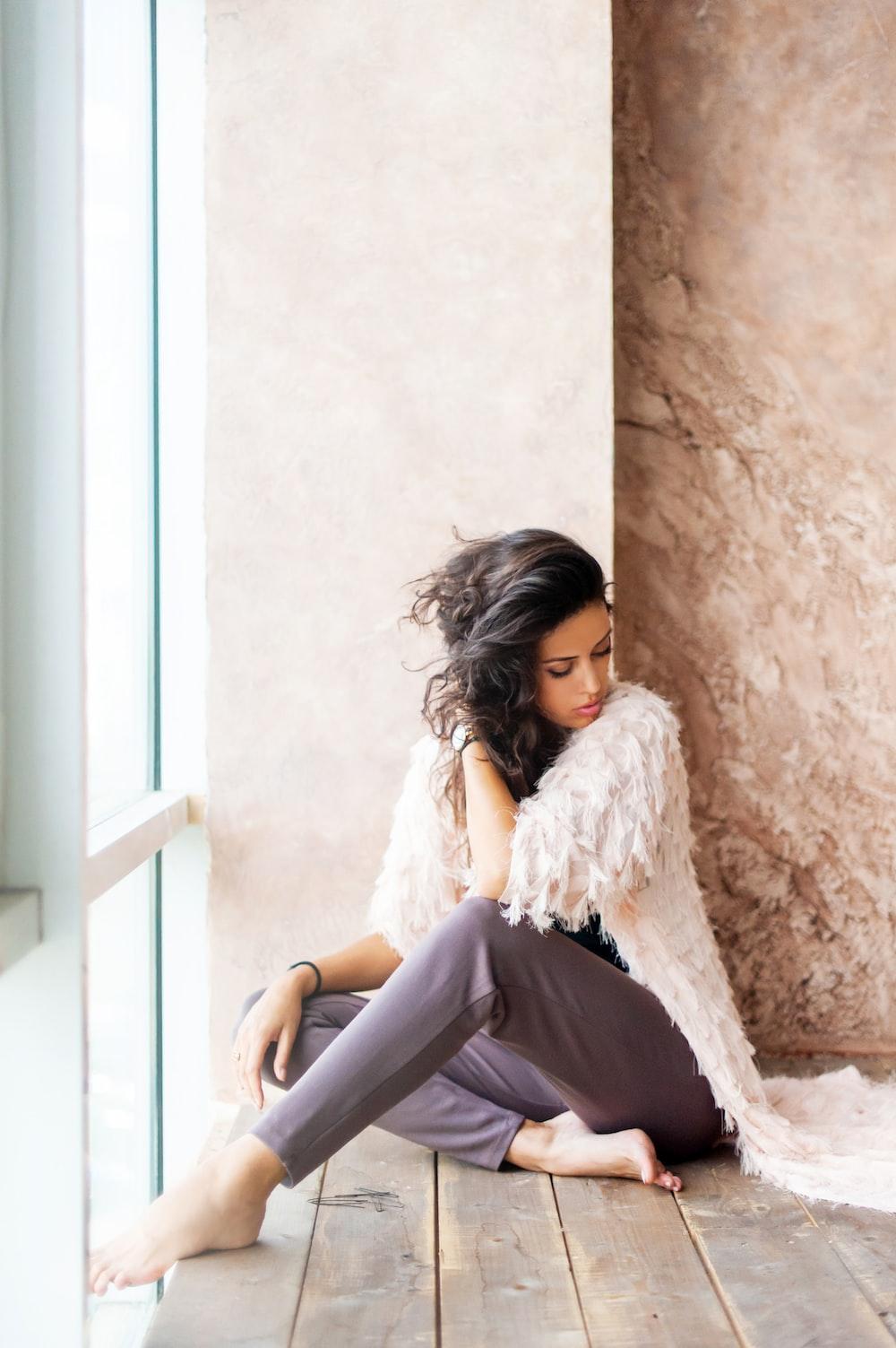 woman sitting beside white wall in front glass window