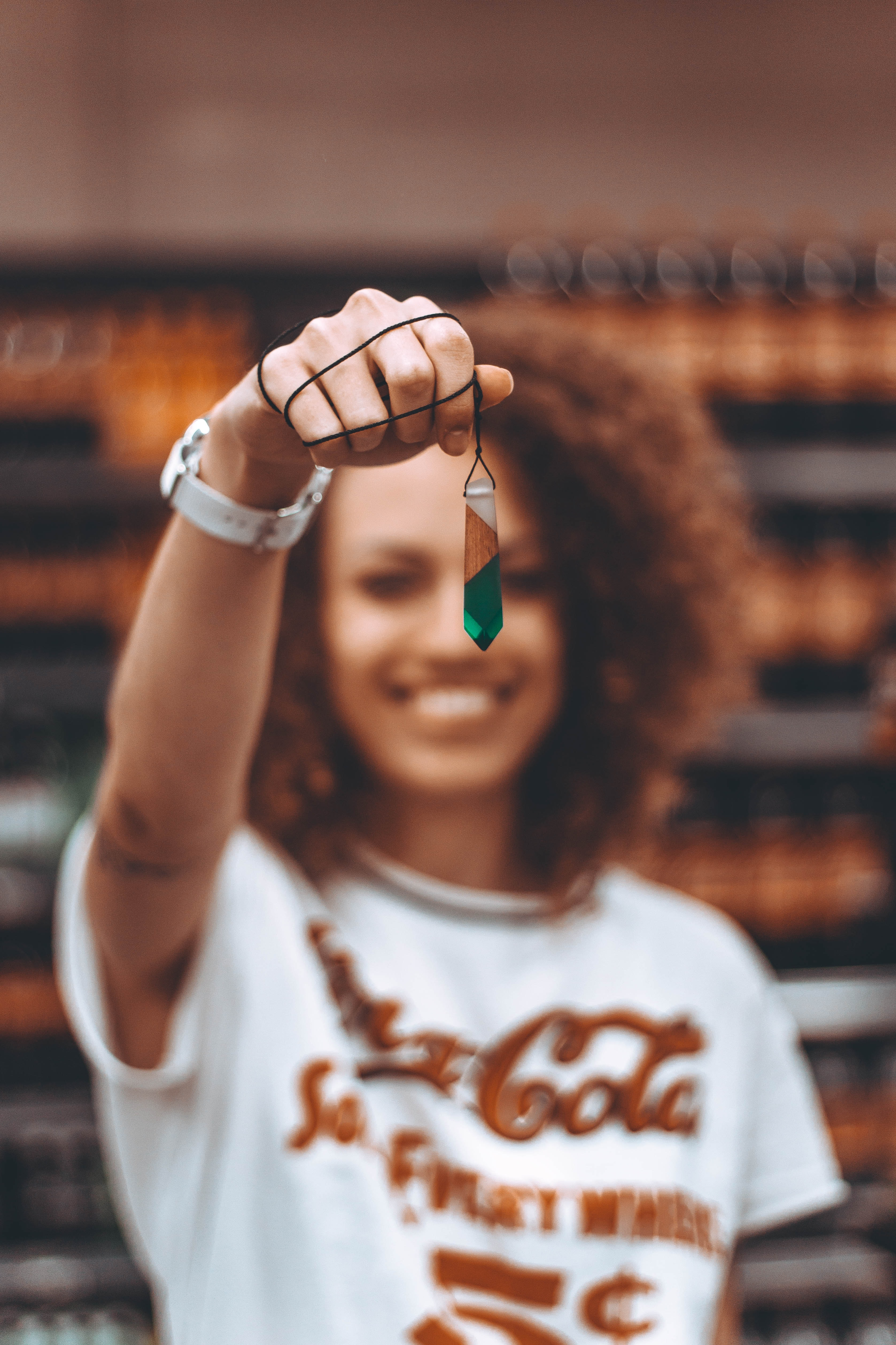 selective focus of woman holding green necklace