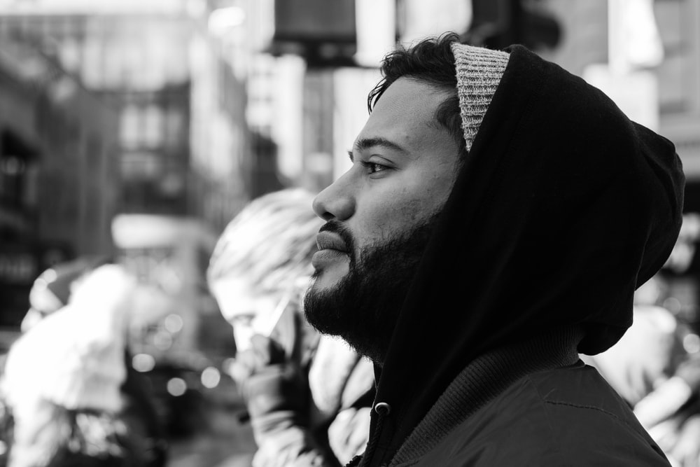grayscale photo of man wearing hooded jacket