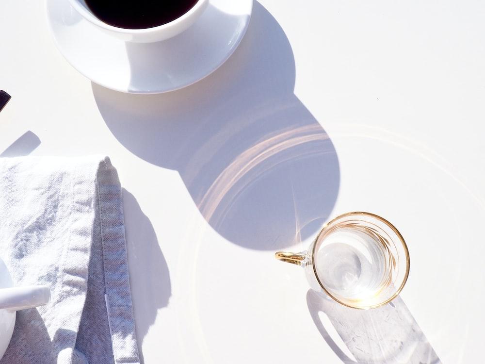clear glass mug beside coffe