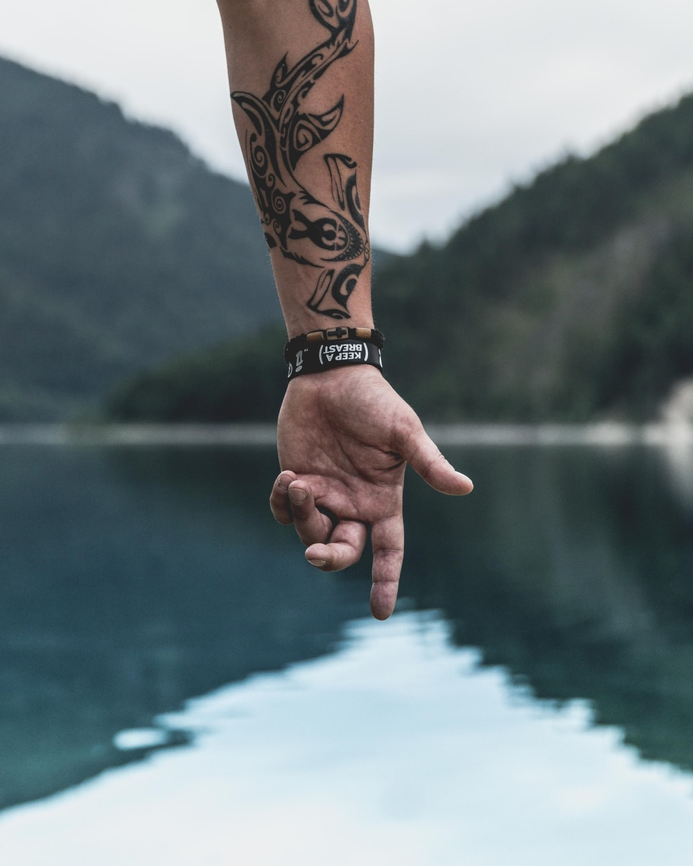 hand of person pointing to body of water with wrist tattoo