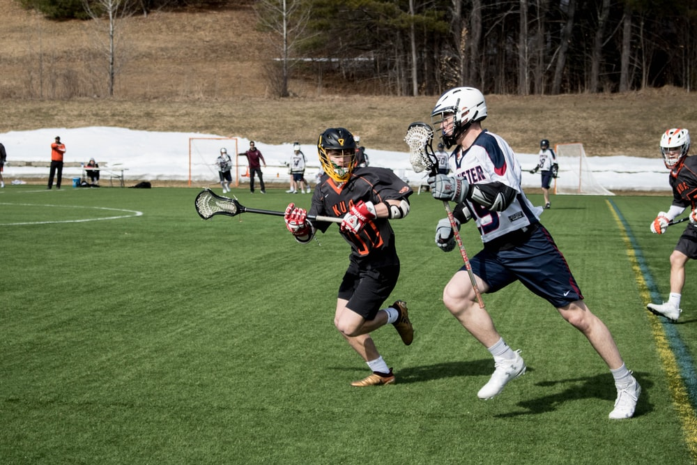 lacrosse players on sports field