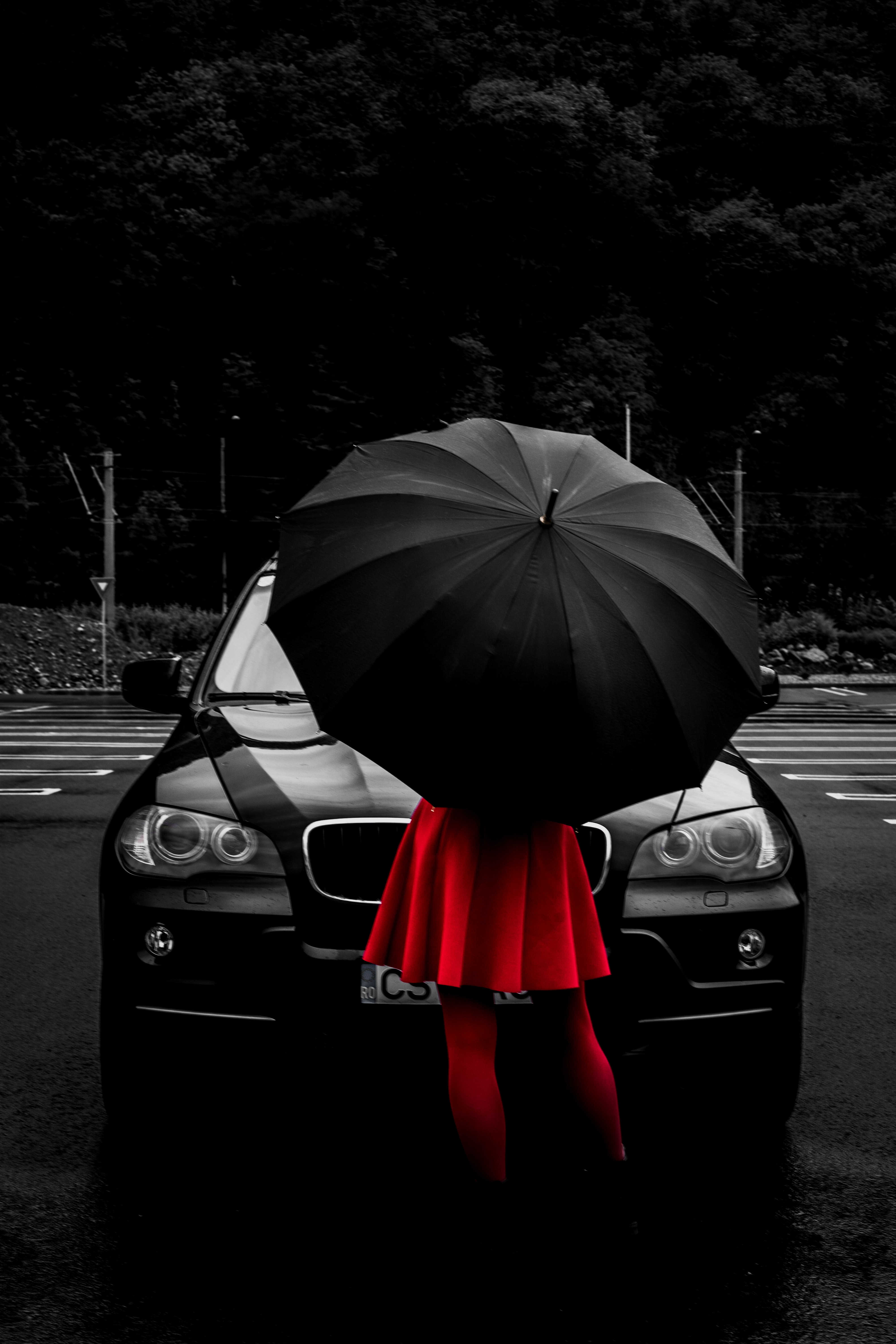 woman wearing red flare dress under black umbrella while standing in front of vehicle
