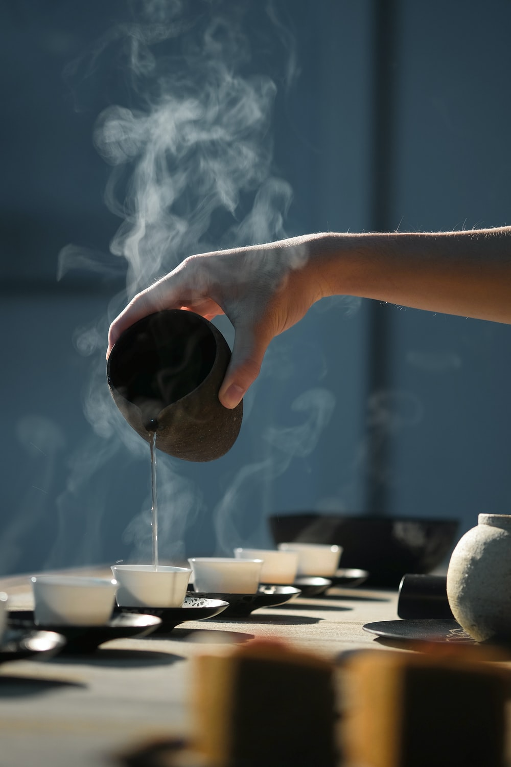 person pouring hot water on white cup
