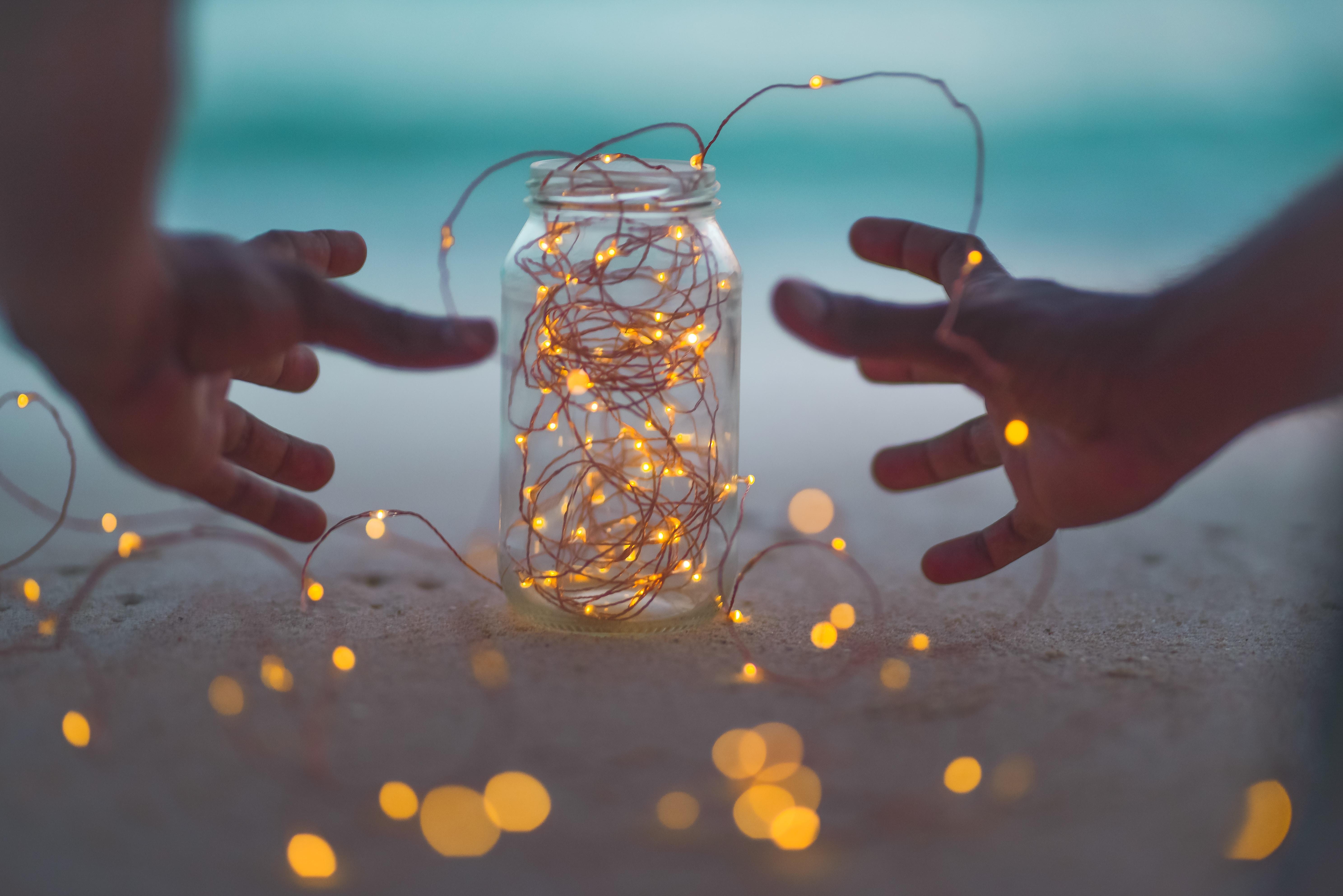 bokeh photography of lighted string lights inside Mason jar
