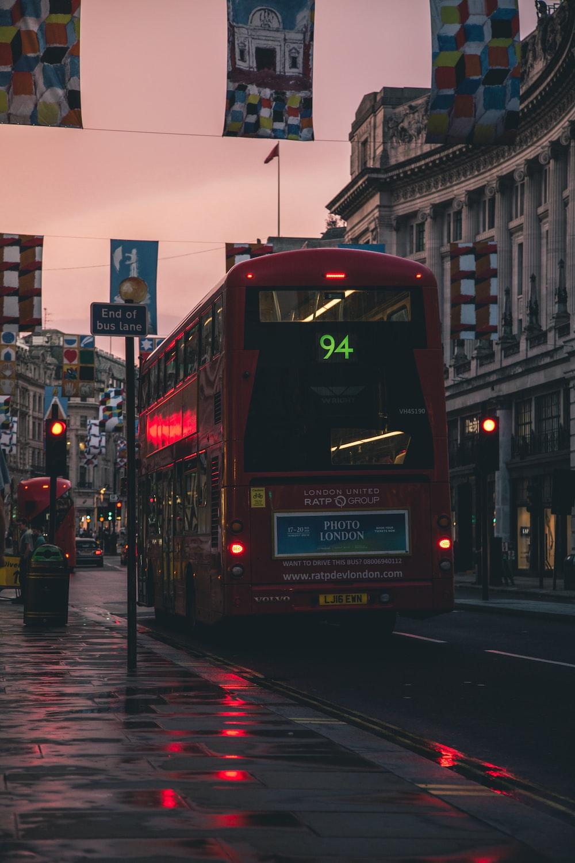 red bus parking beside walkway