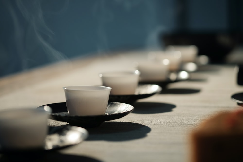 white disposable cups on black saucers