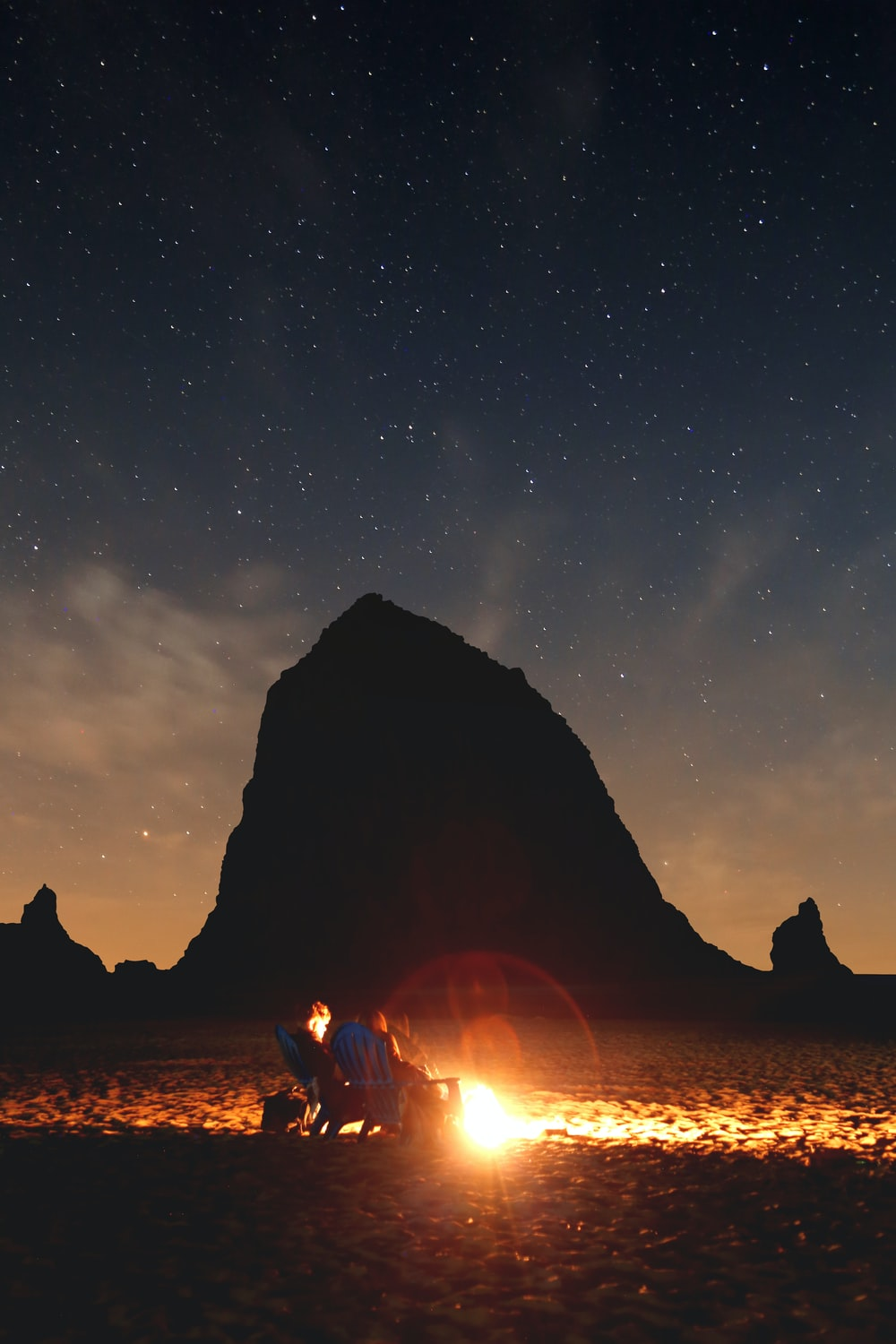 photo of couple sitting in front of bonfire near mountain