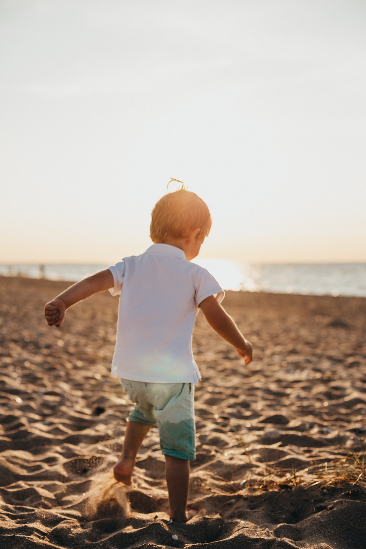 boy standing on sand near sea