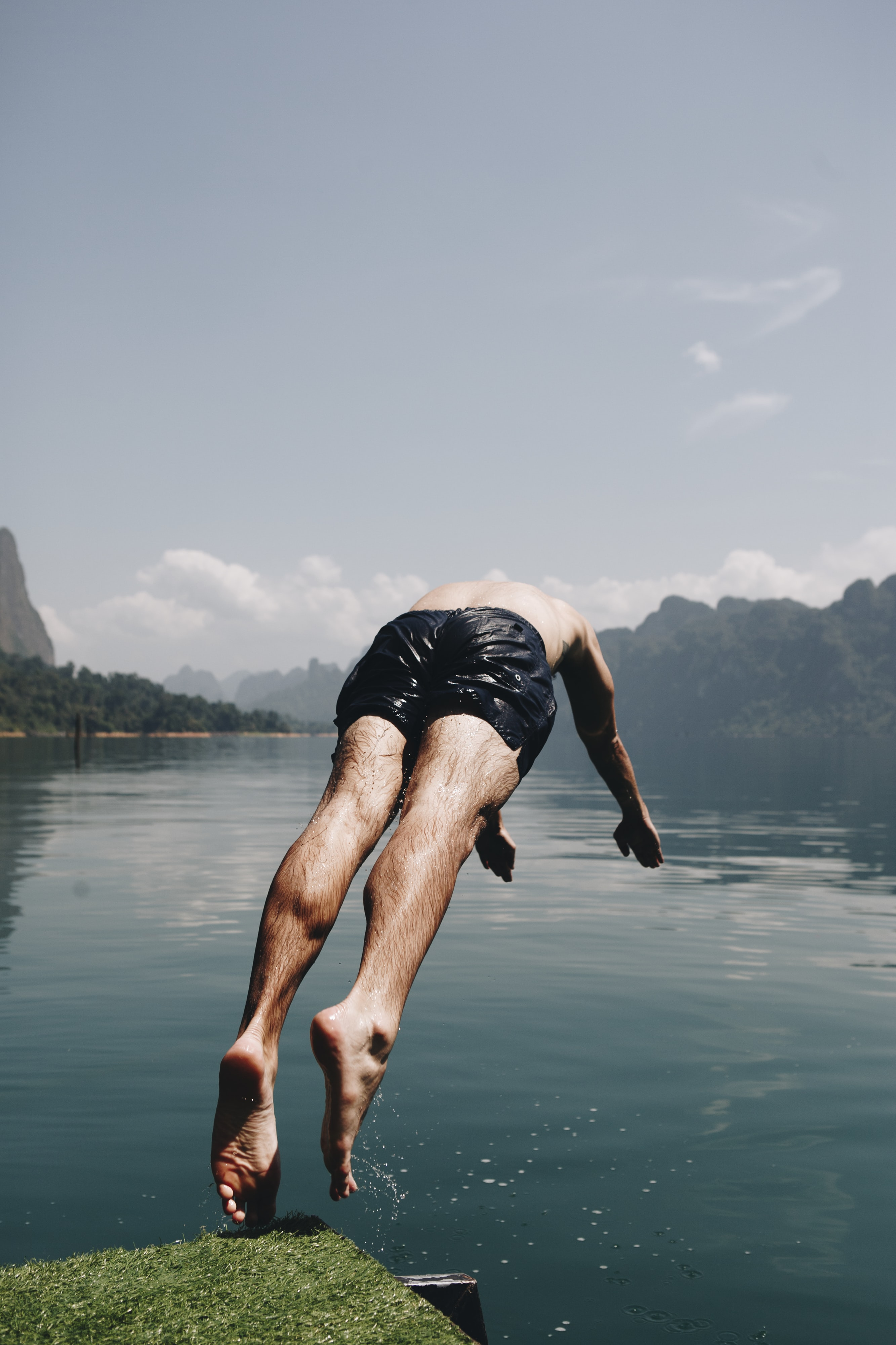 man diving on body of water