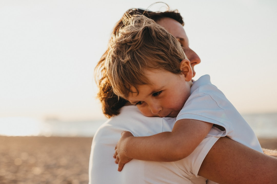 A mother hugging her son tenderly on a beach
