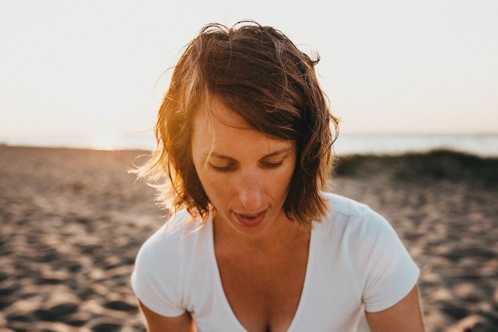 woman sitting on sand near sea shore