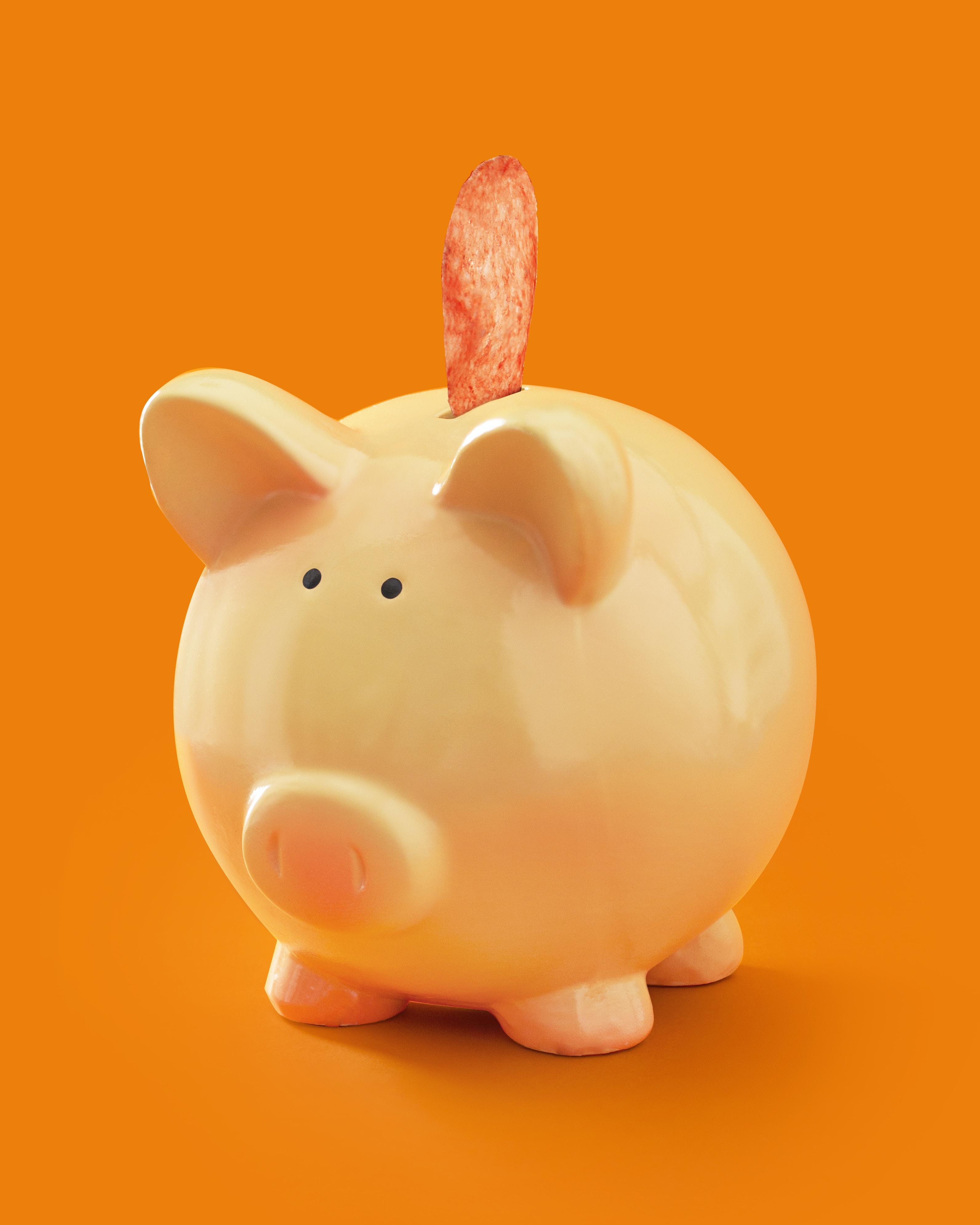 white ceramic piggy bank on orange surface