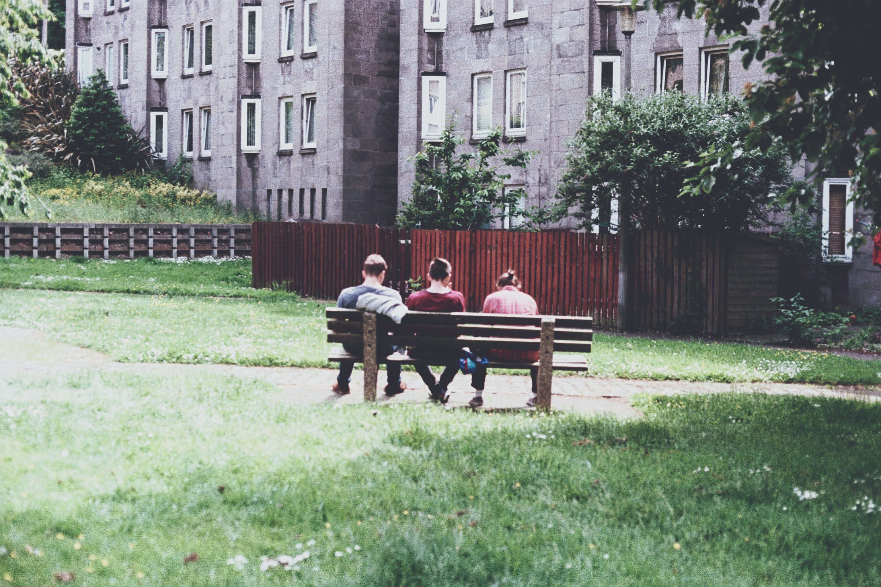 three person sitting on park bench during daytime