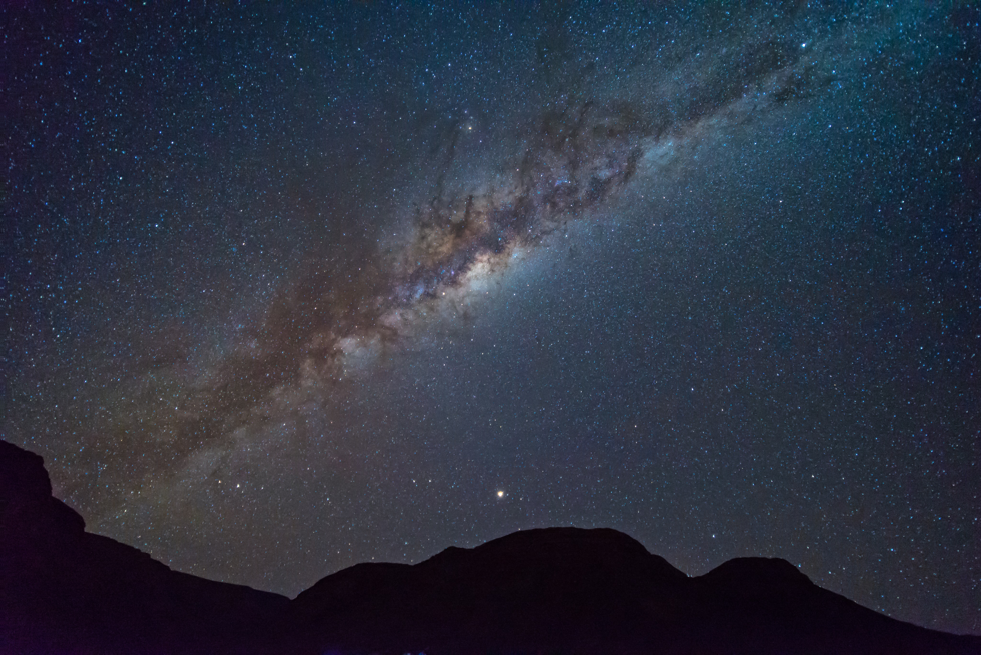 silhouette photograph of mountain under nebula night sky