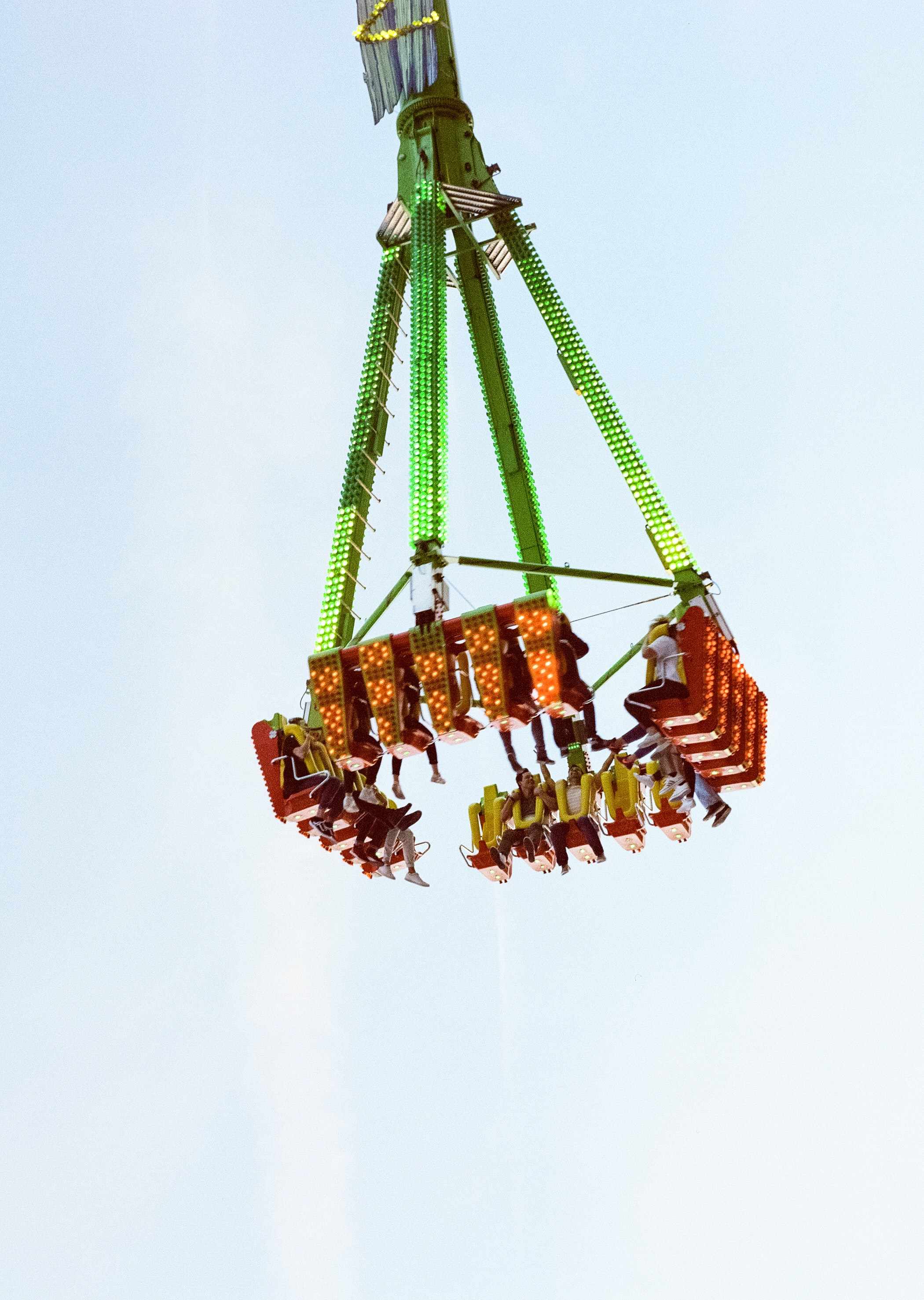 green and orange carnival ride with people