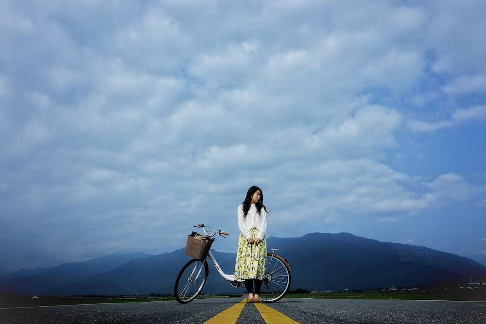 woman standing beside bike on road