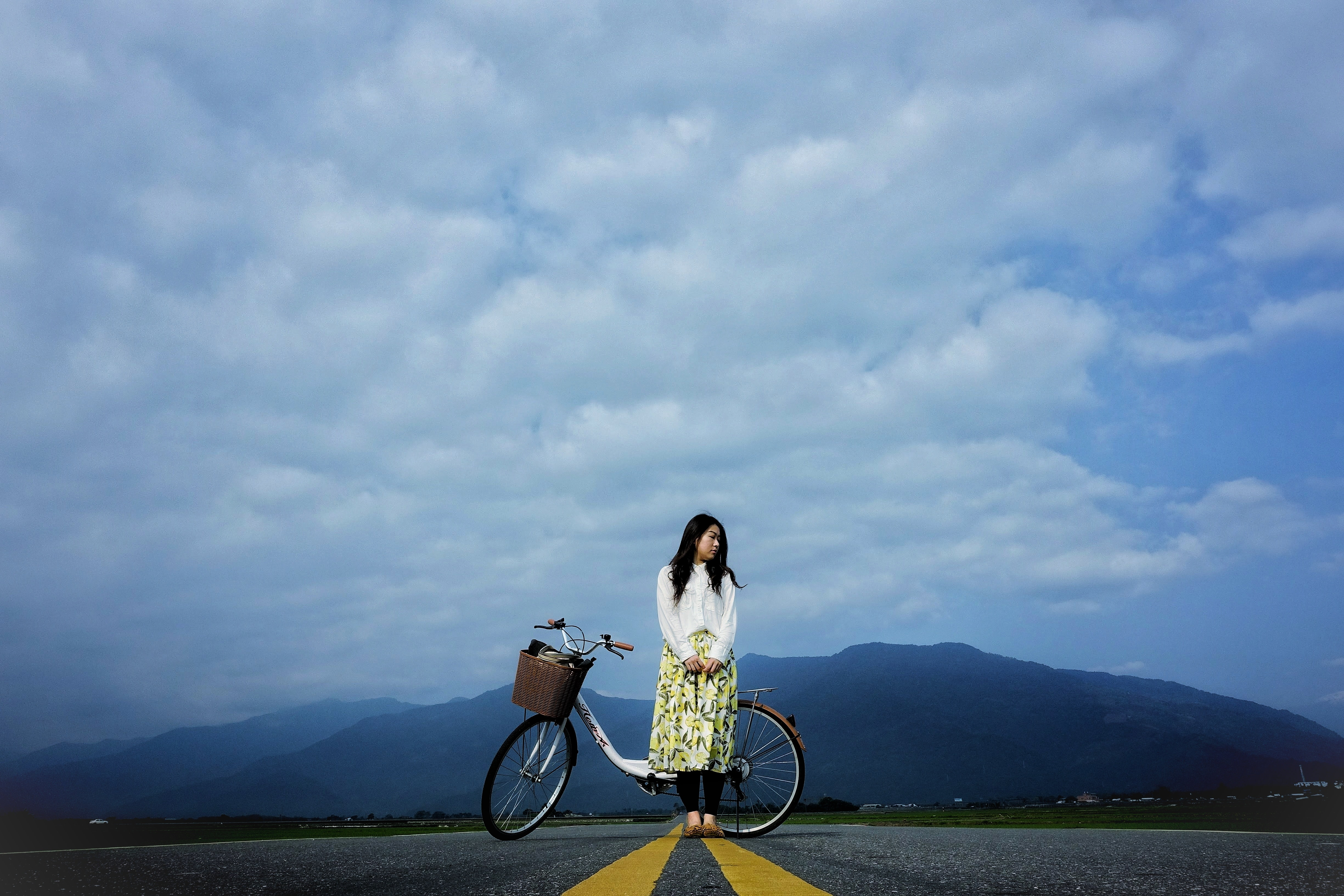 woman standing beside bike on road