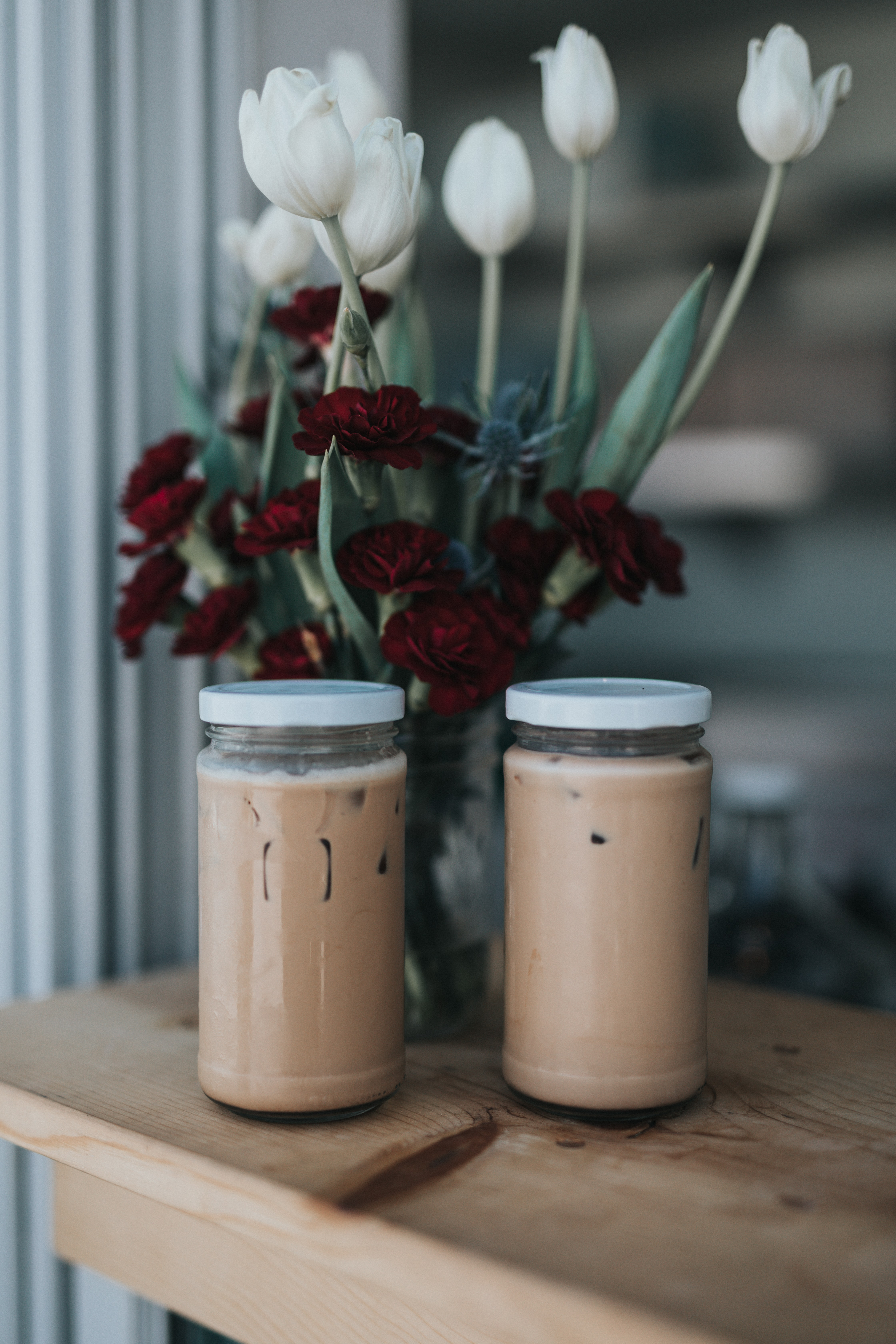 two glass jars on brown surface