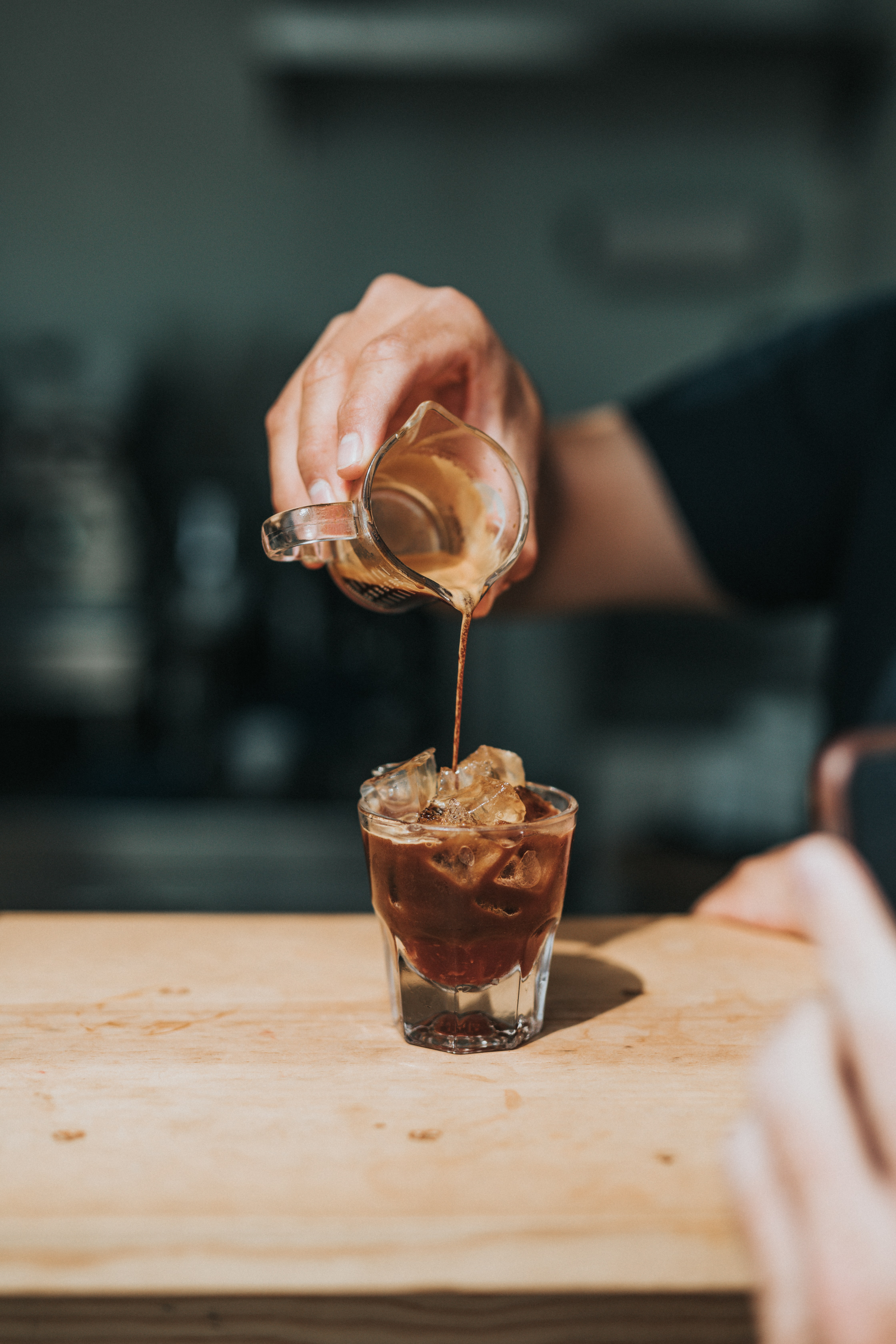 person pouring coffee on rock glass