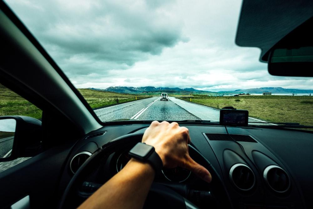 person driving car near vehicle under nimbus cloudes