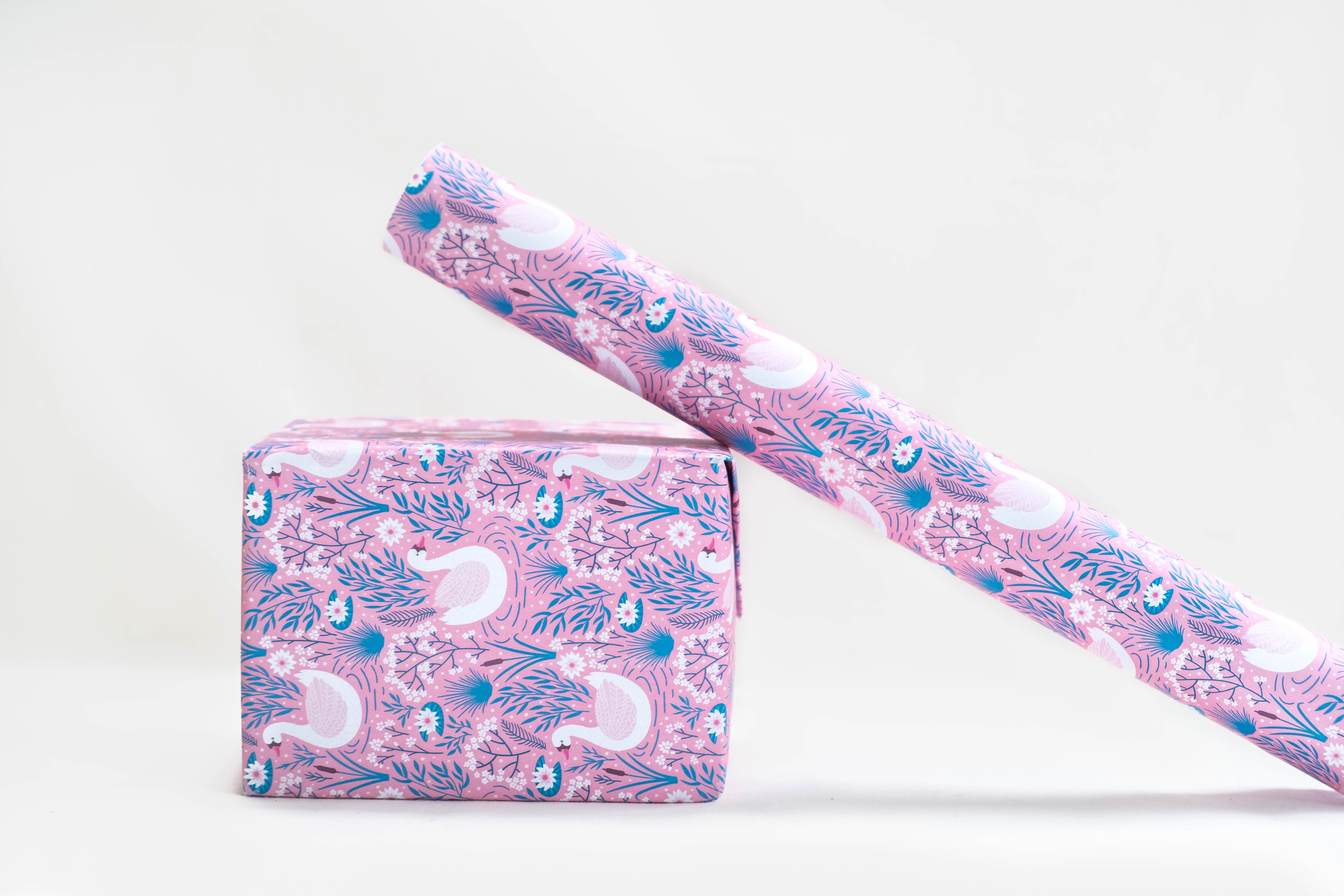 pink, white, and blue floral gift wrap leaning on wrapped box
