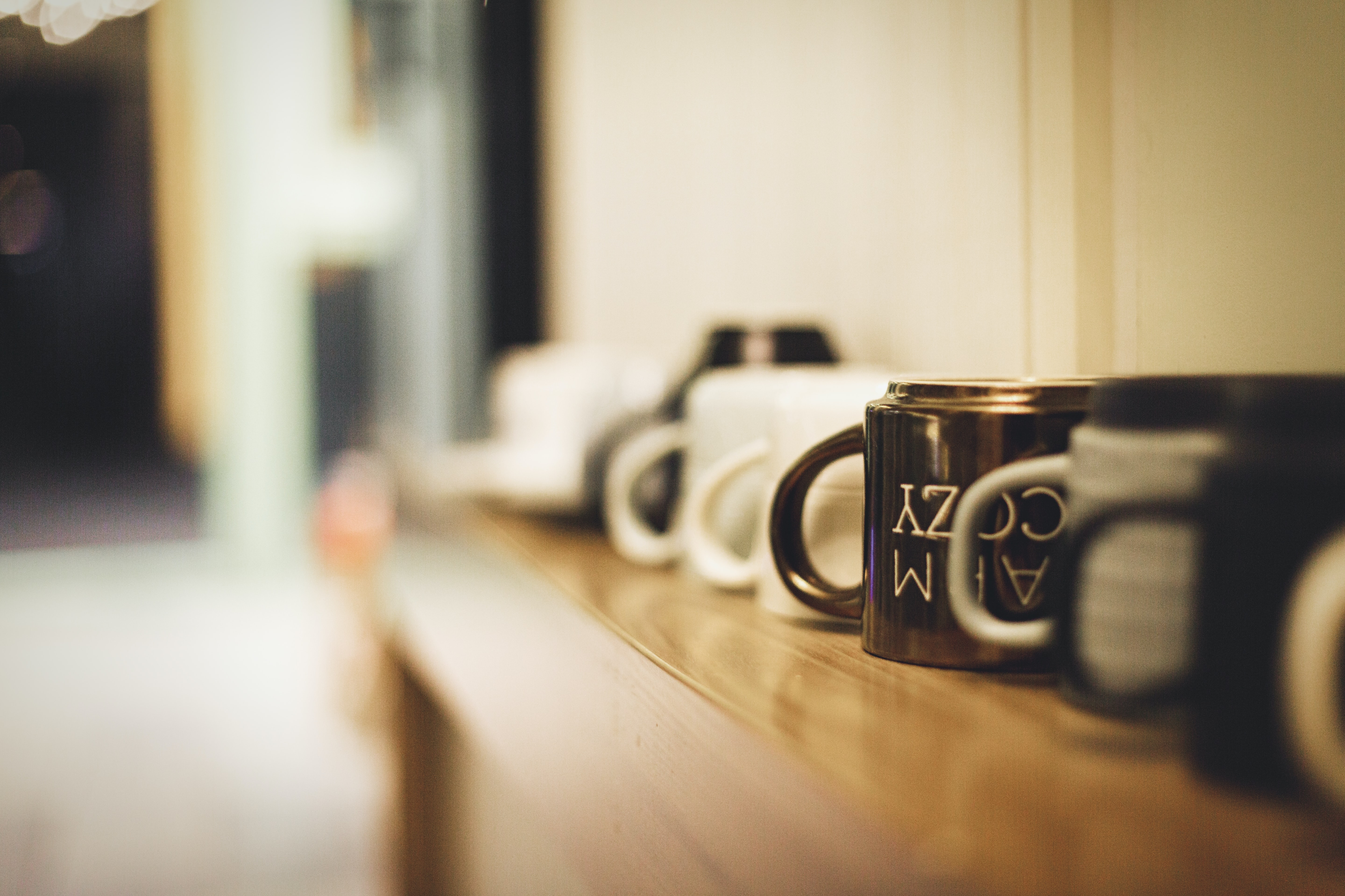 selective focus on white and brown mugs on wooden surface