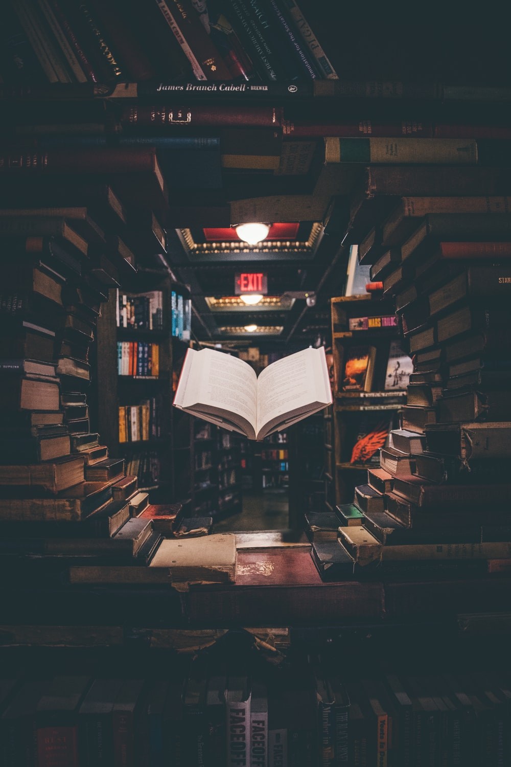view of floating open book from stacked books in library
