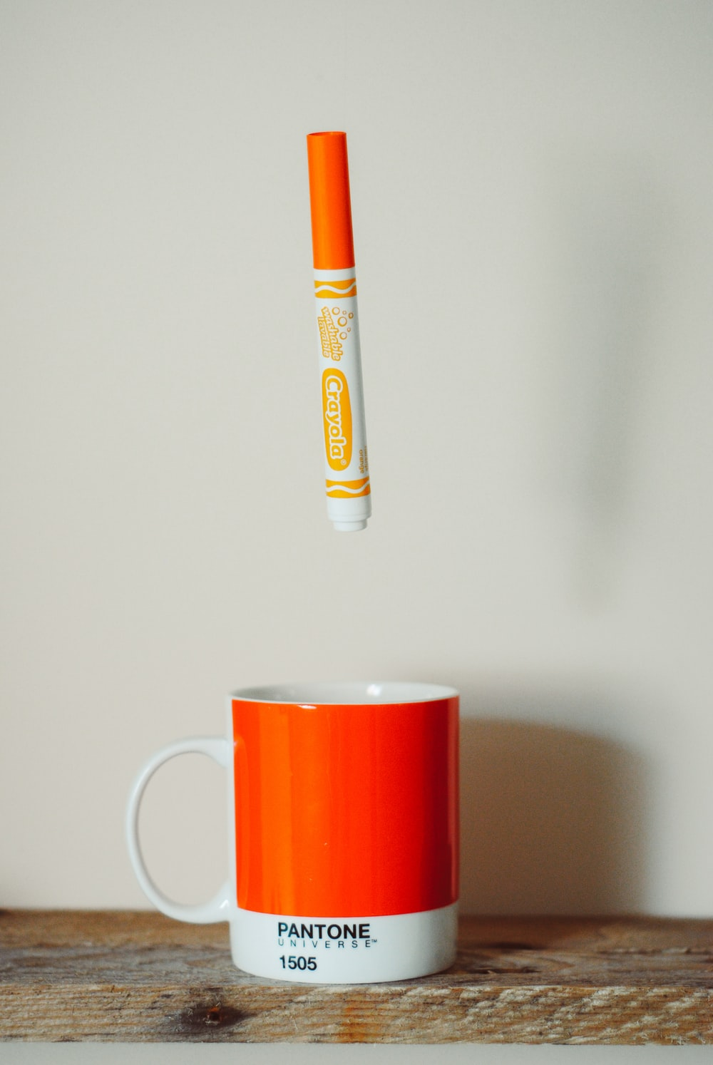 orange Crayola crayon pen above mug
