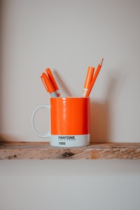 markers in mug on brown surface