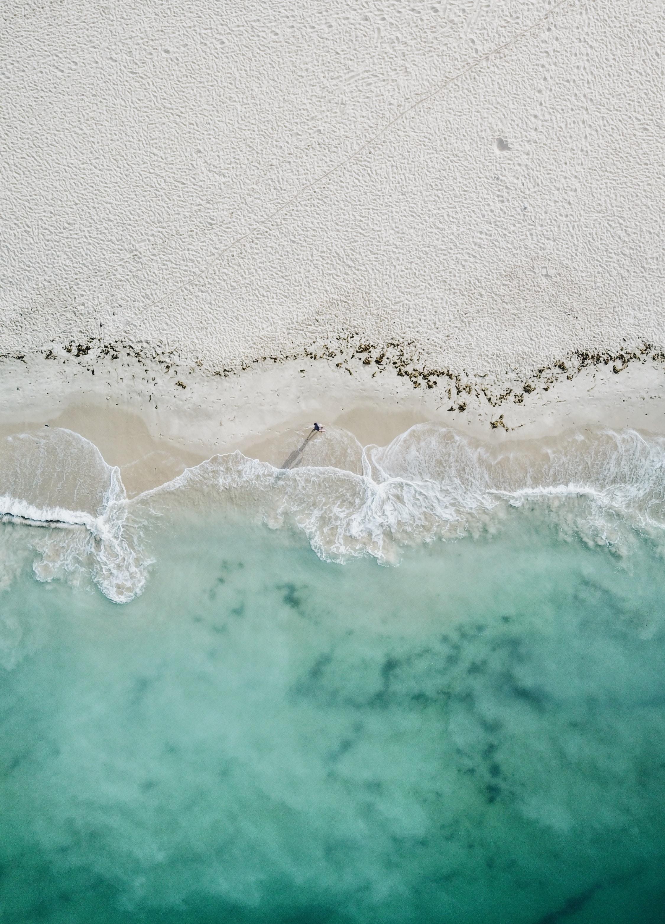 bird's eye photography of person standing on coastline