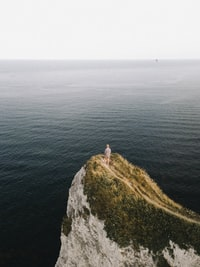man standing on cliff near body of water