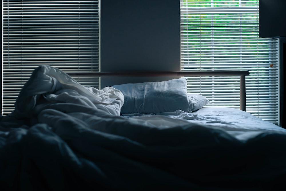 gray bedding beside window blinds