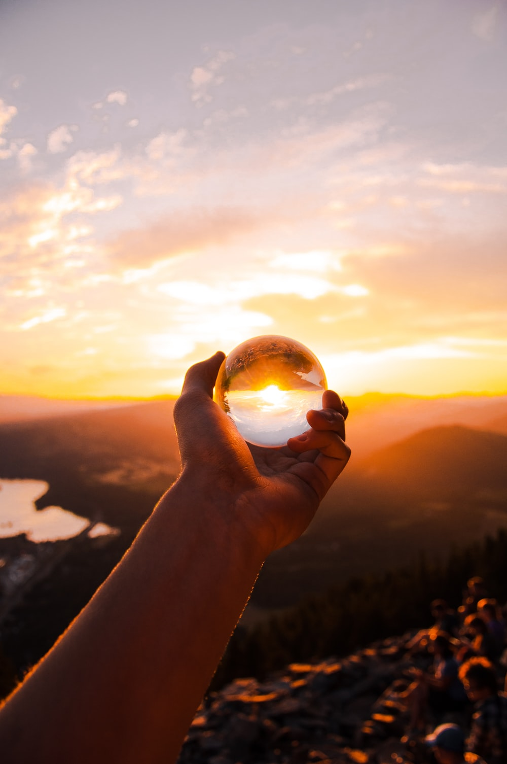 person holding glass ball reflecting sun