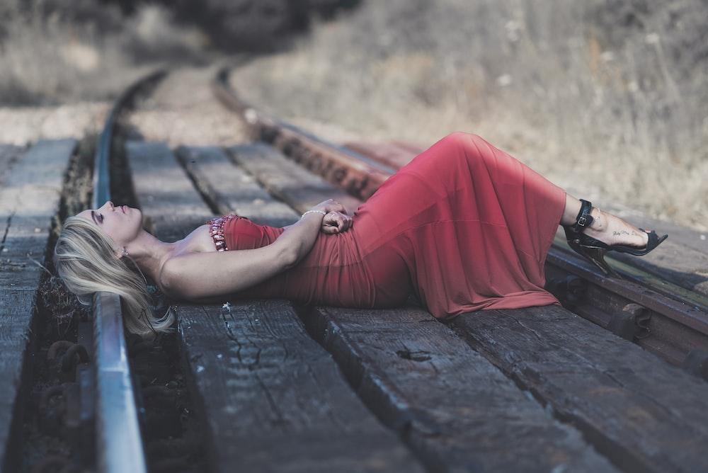 woman lying on train rail