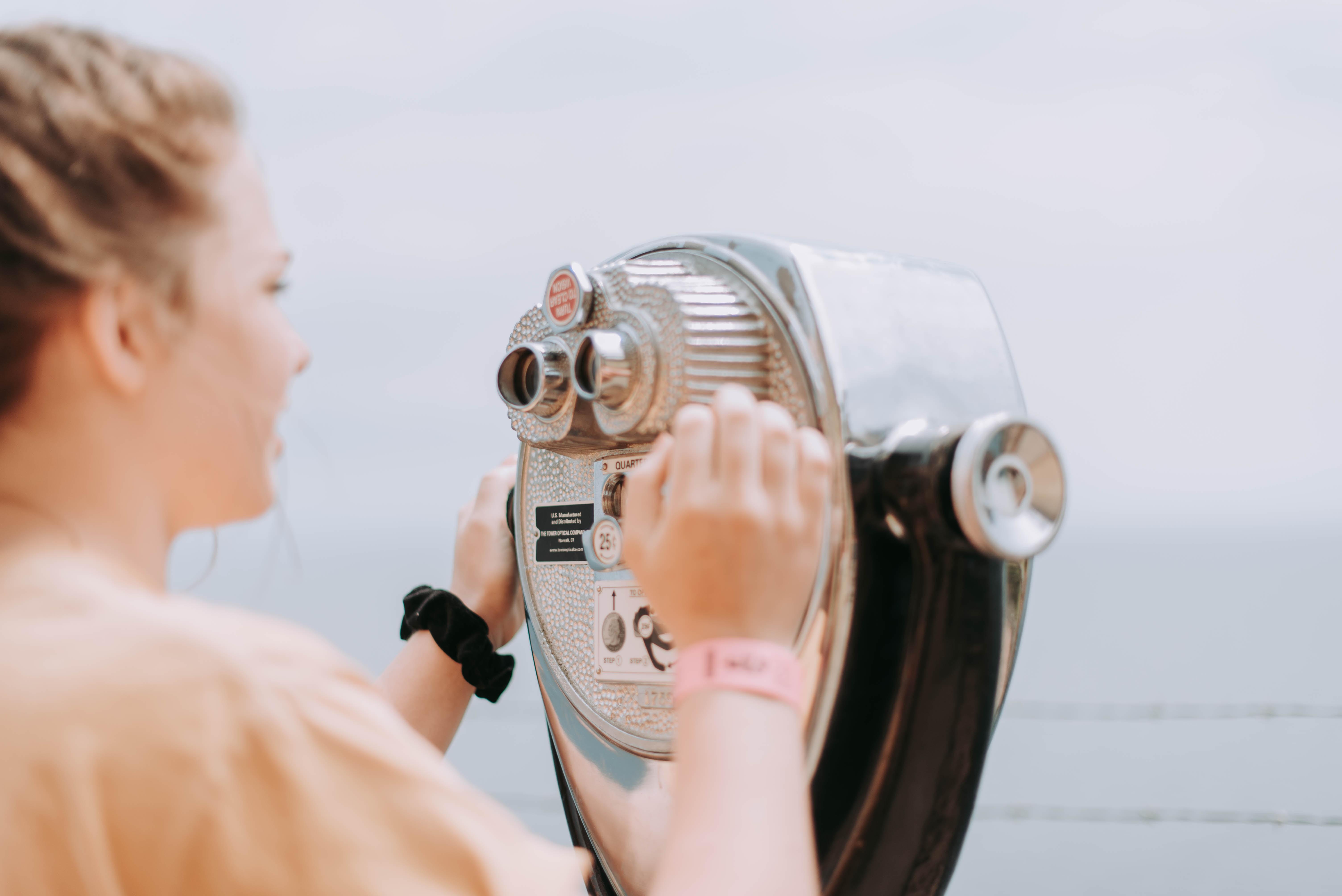 woman holding gray building telescope